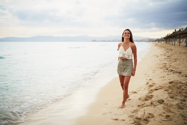 Portret van een lachende jonge vrouw die op het strand loopt en naar de camera glimlacht