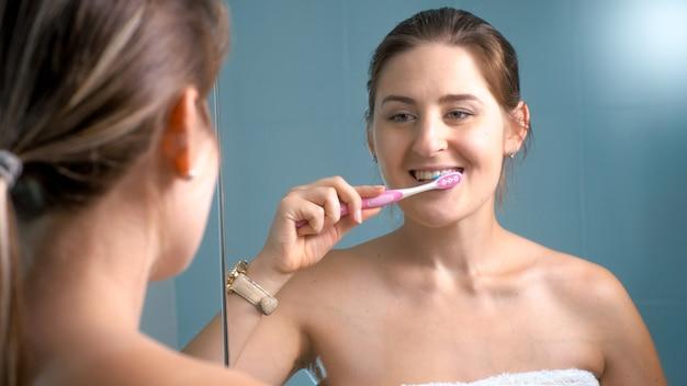 Portret van een lachende jonge vrouw die 's ochtends haar tanden poetst in de badkamer.