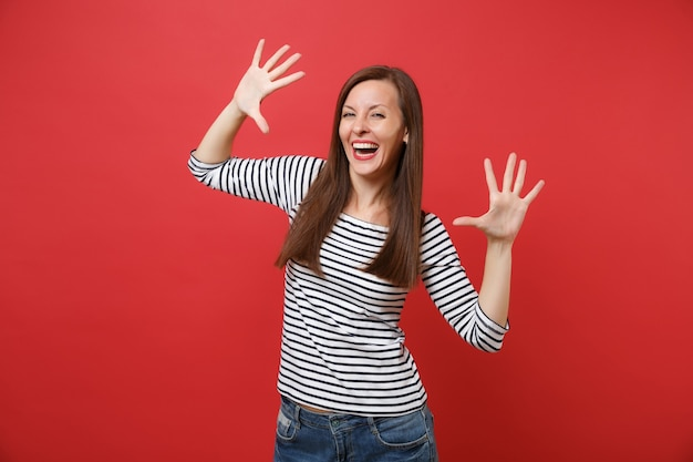 Portret van een lachende jonge vrouw in casual gestreepte kleding die staat en handen, vingers spreidt