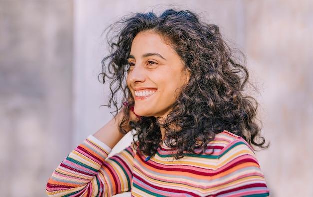 Portret van een lachende jonge vrouw in kleurrijke t-shirt