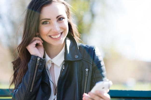 Portret van een lachende jonge vrouw met behulp van oortelefoons aangesloten op een mobiele telefoon.