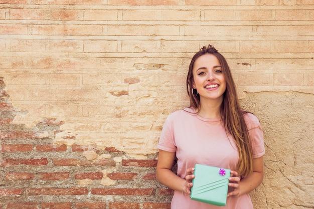 Portret van een lachende jonge vrouw met cadeau voor oude muur
