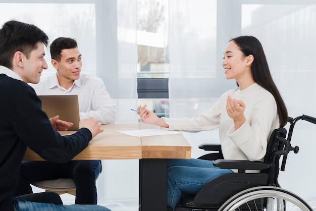 Portret van een lachende jonge vrouw met discussie met zijn mannelijke zakelijke collega in de zakelijke bijeenkomst