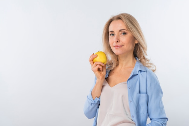 Portret van een lachende jonge vrouw met gele appel in de hand