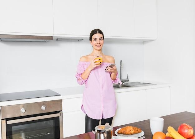 Portret van een lachende jonge vrouw met glas sap en mobiele telefoon in de keuken