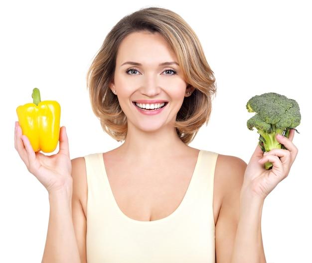 Portret van een lachende jonge vrouw met groenten - geïsoleerd op wit.