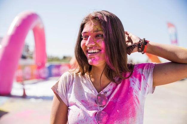 Portret van een lachende jonge vrouw met holi kleur gezicht