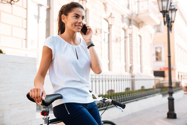 Portret van een lachende jonge vrouw met smartphone op fiets op straat close-up