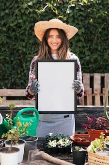 Portret van een lachende jonge vrouw met witte lege frame in de hand