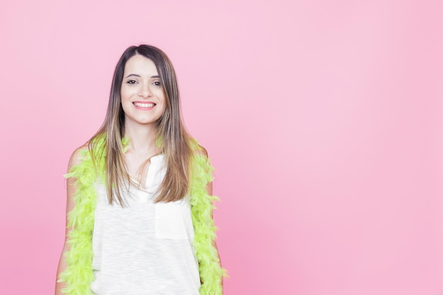 Portret van een lachende jonge vrouw op roze achtergrond