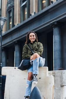 Portret van een lachende jonge vrouw zit in de voorkant van gebouw met tas camera kijken