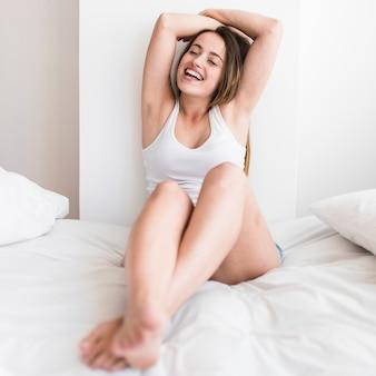 Portret van een lachende jonge vrouw zittend op bed