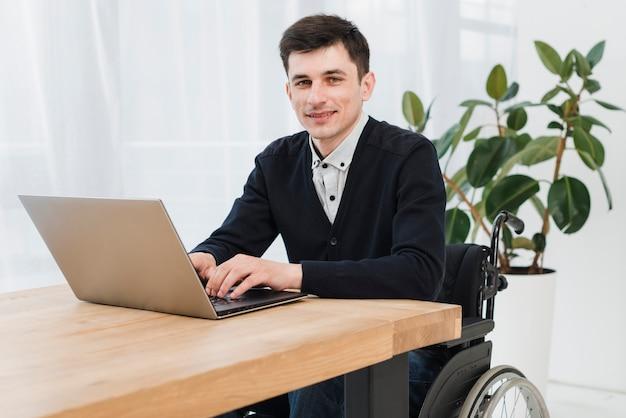 Portret van een lachende jonge zakenman zittend op rolstoel met behulp van laptop