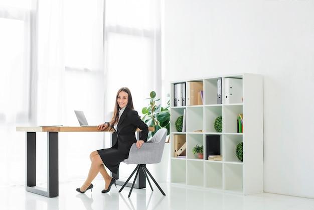 Portret van een lachende jonge zakenvrouw zittend op een stoel camera kijken