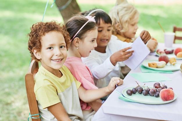 Portret van een lachende jongen die naar de camera kijkt aan de picknicktafel buiten en geniet van een verjaardagsfeestje met vrienden