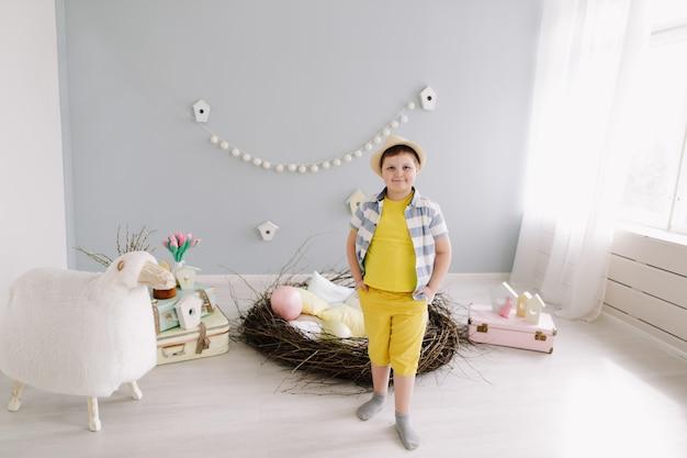 Portret van een lachende jongen in pasen versierde kamer