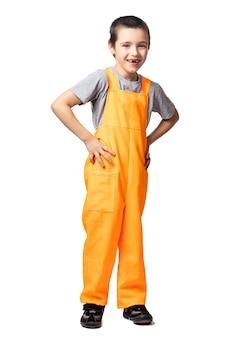 Portret van een lachende jongen timmerman in oranje werk overall houdt handen aan de zijkanten, kijkt sluw en heeft plezier op een witte geïsoleerde achtergrond