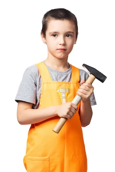 Portret van een lachende jongen timmerman in oranje werk overall poseren, met een hamer in zijn handen plezier op een witte geïsoleerde achtergrond. kinderkostuum voor de feestdagen