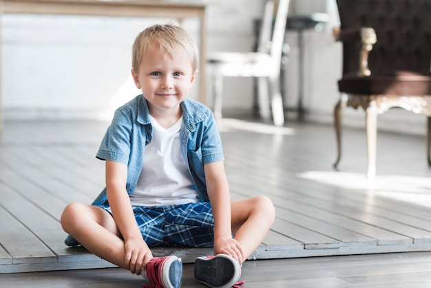 Portret van een lachende jongen zittend op de vloer thuis