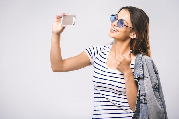 Portret van een lachende leuke vrouw in zonnebril selfie foto maken op smartphone