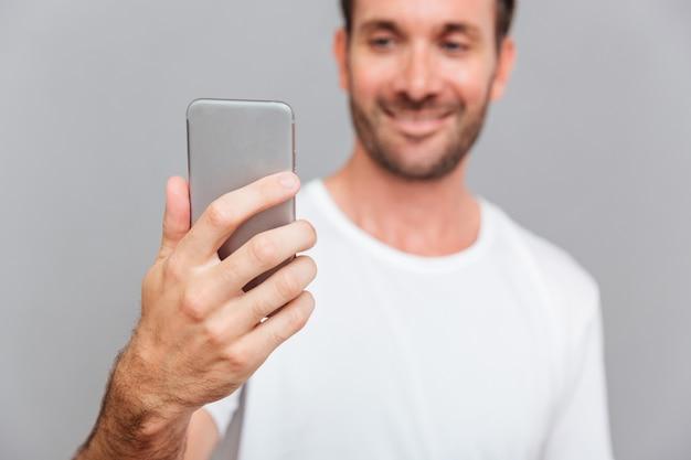 Portret van een lachende man die selfie foto maakt over grijze achtergrond