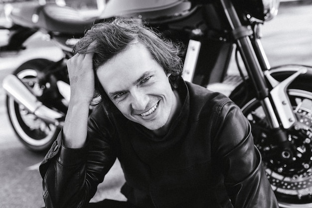 Portret van een lachende man die zijn haar op de achtergrond van een motorfiets fixeert zwart-witfotografie
