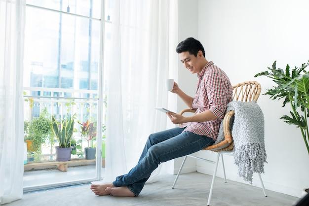 Portret van een lachende man ontspannen op stoel nieuw raam met behulp van tafel en koffiekopje te houden.
