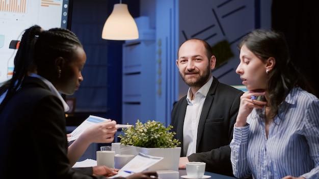 Portret van een lachende manager die 's avonds laat naar de voorkant kijkt en werkt aan de bedrijfsstrategie in de vergaderruimte