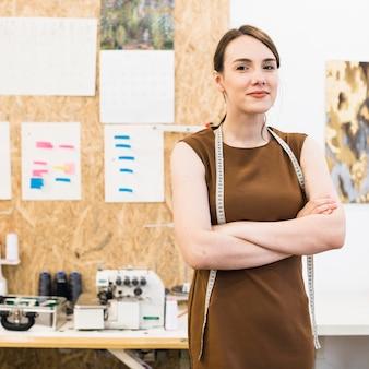 Portret van een lachende modeontwerper met gevouwen handen
