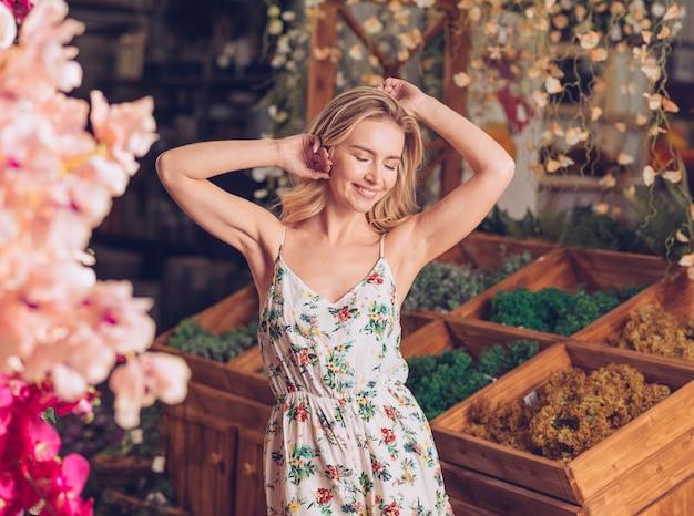 Portret van een lachende mooie jonge vrouw ontspannen in de winkel van de bloemist