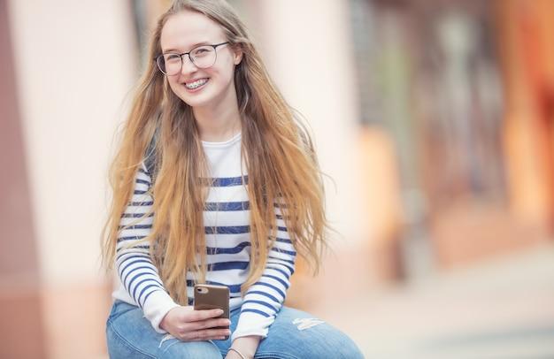 Portret van een lachende mooie tienermeisje met beugels. jong schoolmeisje met schooltas en mobiele telefoon.