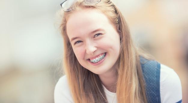 Portret van een lachende mooie tienermeisje met beugels.