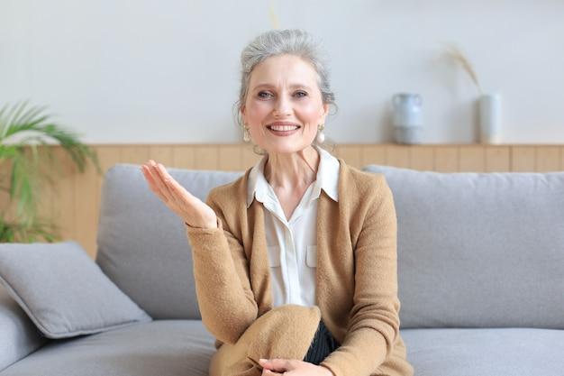 Portret van een lachende mooie vrouw van middelbare leeftijd die naar de camera kijkt, een videogesprek voert, een sollicitatiegesprek of online dating heeft.