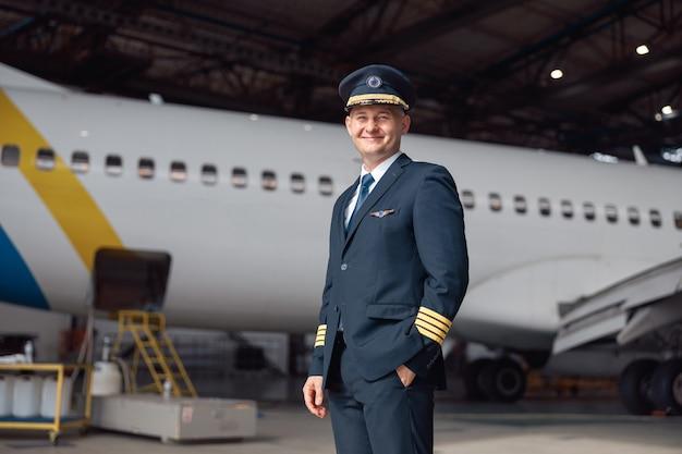 Portret van een lachende piloot in uniform die naar de camera kijkt, staande voor een groot passagiersvliegtuig in de hangar van de luchthaven. vliegtuigen, beroep, transportconcept