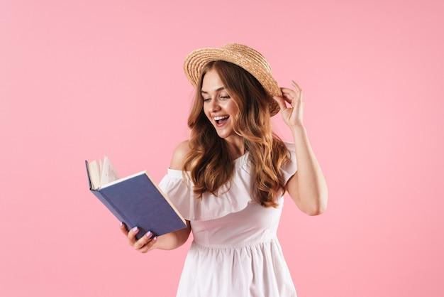 Portret van een lachende schattige jonge mooie vrouw poseren geïsoleerd over roze muur leesboek.