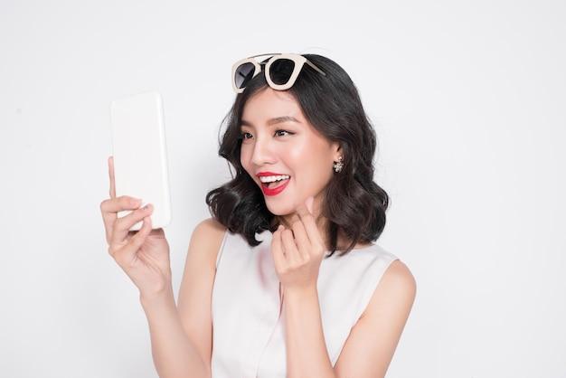 Portret van een lachende schattige vrouw die selfie foto maakt op smartphone geïsoleerd op een witte achtergrond
