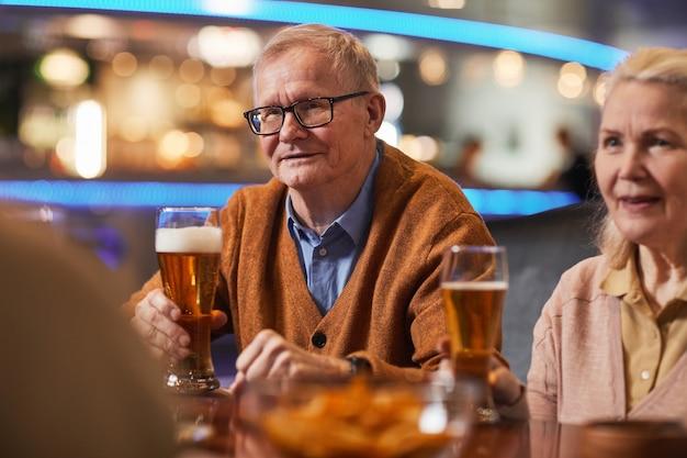 Portret van een lachende senior man die bier drinkt in de bar terwijl hij geniet van een avondje uit met vrienden, kopieer ruimte