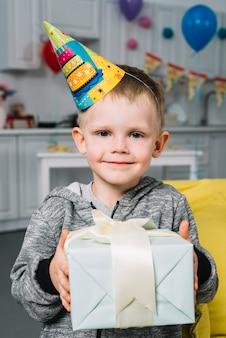 Portret van een lachende verjaardag jongen bedrijf gewikkeld geschenk doos in de hand te houden