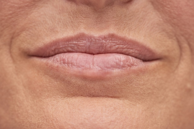 Portret van een lachende volwassen vrouw met een perfecte huid en mooie lippen