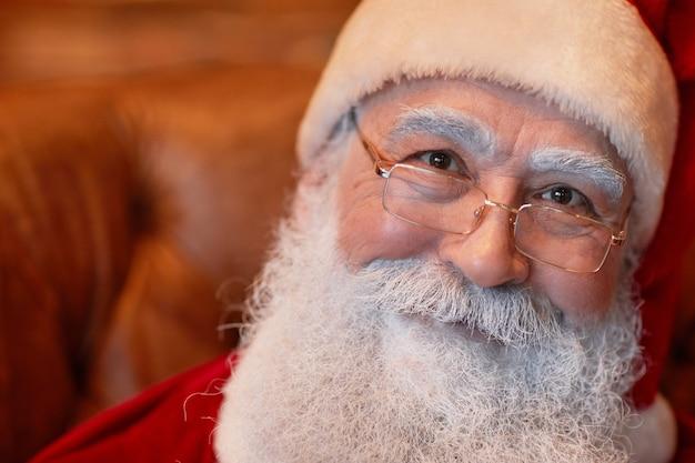 Portret van een lachende vriendelijke senior kerstman met witte baard en wenkbrauwen met een bril en pet