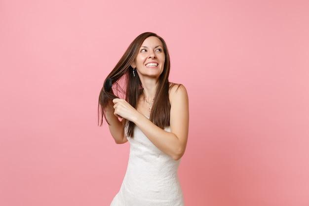 Portret van een lachende vrolijke vrouw in een mooie witte jurk die een kam vasthoudt en haar haar kamt