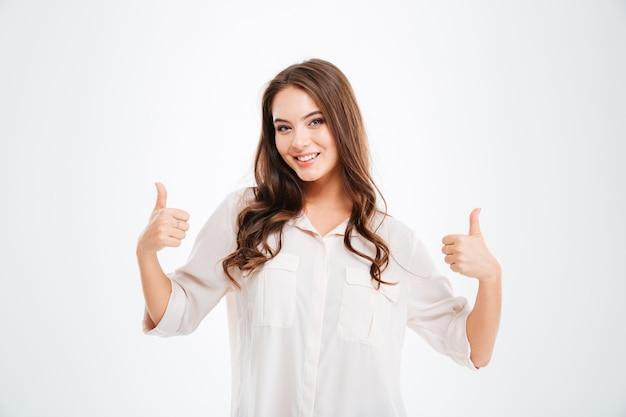 Portret van een lachende vrouw die duimen toont geïsoleerd op een witte muur