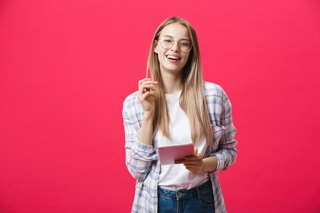 Portret van een lachende vrouw die tabletcomputer met behulp van die op een roze achtergrond wordt geïsoleerd en camera bekijkt
