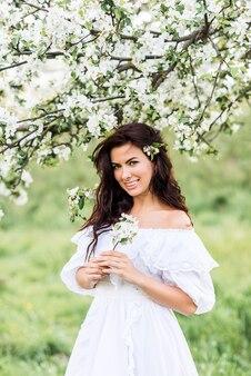 Portret van een lachende vrouw in een bloeiende tuin. een meisje lacht in de lentetuin.