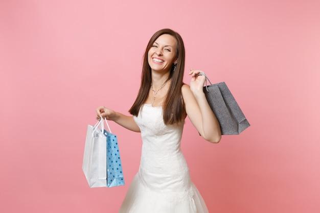 Portret van een lachende vrouw in witte kanten jurk met veelkleurige pakketten met aankopen na het winkelen
