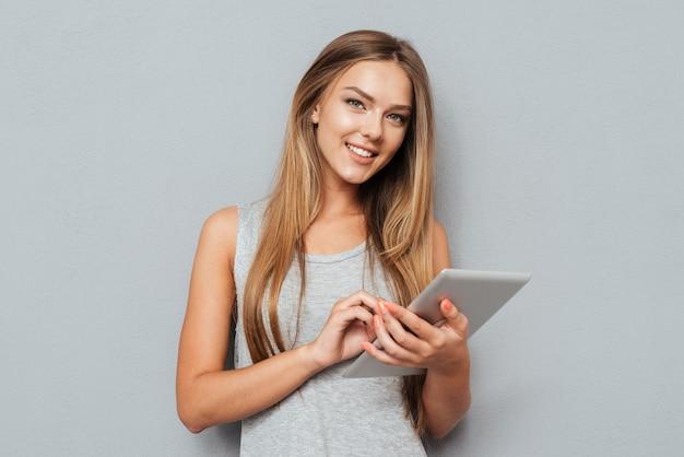 Portret van een lachende vrouw met behulp van tabletcomputer geïsoleerd op een grijze achtergrond en camera kijken