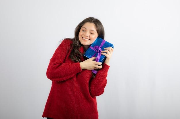 Portret van een lachende vrouw met een kerstcadeaudoos met paars lint.