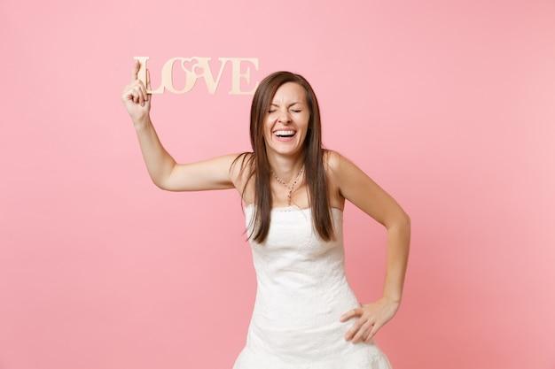 Portret van een lachende vrouw met gesloten ogen in een witte jurk die staat met een arm over elkaar heen met houten woordletters love