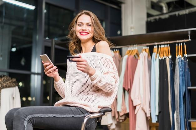 Portret van een lachende vrouw zitten in de winkel houden creditcard en mobiele telefoon in de hand