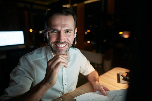 Portret van een lachende zakenman die laat in zijn kantoor werkt